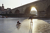 Mother and child on frozen river Danube, Stony Bridge, Regensburg, Upper Palatinate, Bavaria, Germany