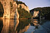 Sonnenbeschienene Kalksteinklippen spiegeln sich in der Donau, Niederbayern, Bayern, Deutschland