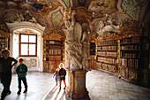 Kinder bestaunen die Figuren an einem Gewölbepfeiler in der barocken Bibliothek der Benediktinerabtei Metten, Niederbayern, Bayern, Deutschland