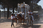 Procession of pilgrims on horseback and on foot, a mule driven cart with an altar, Huelva province, Costa de la Luz, Andalusia, Spain