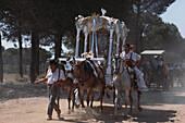 Zug von Pilgern zu Pferde und zu Fuss, Maultierkarren mit einem Altar, Provinz Huelva, Costa de la Luz, Andalusien, Spanien