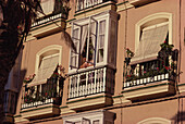 A woman looking out of her bay-window in Cadiz, Andalusia, Spain