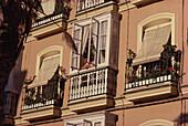 Eine Frau schaut aus dem Fenster ihres Hauses in Cádiz, Andalusien. Spanien