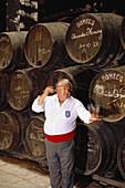 Ein Weinprüfer gießt Sherry in Probiergläser vor einem Stapel Sherry Fässer, Faßkeller der Bodegas Pedro Domeq, Jerez de la Frontera, Provinz Cádiz, Andalusien. Spanien