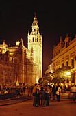 Menschen stehen abends vor dem beleuchteten Glockenturm der Kathedrale Santa Maria de la Sede, Plaza Triunfo, Sevilla, Andalusien, Spanien