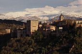 The Alhambra, Moorish palace in front of snow covered mountain range Sierra Nevada, Granada, Andalusia, Spain