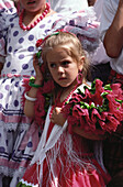 Little girl in a colourful frilly dress at the feast of Corpus Christi, Granada, Andalusia, Spain
