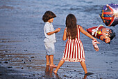A boy and a girl playing bare-footed with balloons at the beach of Giniginamar, Fuerteventura, Canary Islands, Spain