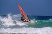 A sailboarder riding the waves of the surf, Jandia Peninsula, Fuerteventura, Canary Islands, Spain