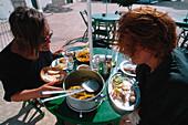 Two women eating fish dish at outdoor seating of a bar at Puerto de la Luz, Jandia Peninsula, Fuerteventura