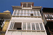 Glazed white wooden balconies at the facade of a traditional house in Comillas, Cantabria, Spain