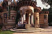 Young people sitting at the portico of Villa El Capricho, Comillas, Cantabria, Spain