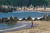 Spiky rocks and bathing people at the sandy beach Playa de Toro, Llanes, Asturias, Costa Verde, Bay of Biscay, Northern Spain