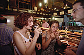 Two young women and a young man drinking wine and tasting some tapas from the counter in a bar in Valladolid, Castilla-Leon, Northern Spain