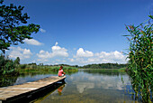 Woman sitting on landing stage at lake Fohnsee, Osterseen, Upper Bavaria, Bavaria, Germany