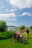 bathers with bikes at shore of lake Kochelsee and man with mobile phone, Upper Bavaria, Bavaria, Germany