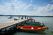 People on landing stage with rowings boats, lake Simssee, Chiemgau, Upper Bavaria, Bavaria, Germany
