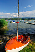 Sailing boat at shore, sailing boats and landing stage in background, lake Simssee, Chiemgau, Upper Bavaria, Bavaria, Germany
