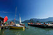 Landing stage with sailing boats and bathers at lake Mondsee, Salzkammergut, Upper Austria, Austria