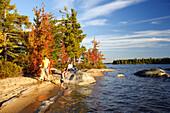 Family on a beach on Lake Millinocket in autumn, Maine, ,USA