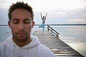 Man with closed eyes, woman practising yoga on yetty at Lake Starnberg, Muensing, Bavaria, Germany