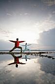Couple practising yoga at Lake Starnberger, Muensing, Bavaria, Germany, MR