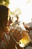 Mid adult woman drinking a glass of beer, beergarden Buchscharn, Muensing, Lake Starnberg, Bavaria, Germany, MR