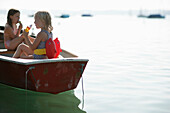 Two girls eating ice cream in a rowing boat, Lake Woerthsee, Bavaria, Germany, MR