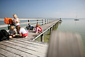 Children playing on jetty at Lake Ammersee, Utting, Bavaria, Germany