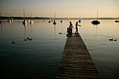Children on jetty at Lake Woerthsee, Bavaria, Germany, MR