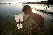 Boy playing with a toy float in lake Wörthsee, Bavaria, Germany, MR