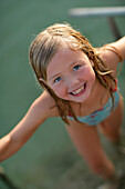 Girl coming out of Lake Woerthsee and smiling at camera, Walchstadt, Bavaria, Germany, MR