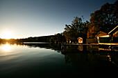 Wooden boat houses at the waters edge at dusk, Walchstadt, Lake Wörthsee, Upper Bavaria, Bavaria, Germany