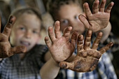 Two boys in the barn, showing dirty hands, Walchstadt, Upper Bavaria, Germany