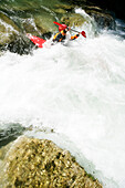 Man paddling through whitewater, kayak weekend for beginners on the Mangfall river, Upper Bavaria, Germany