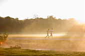 Couple jogging in the English Garden in the morning, Munich, Bavaria, Germany