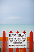 Sign on a fence of a private beach, North Sea, Germany