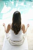 Woman practising yoga near a pool, Styria, Austria