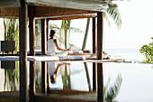 Frau beim Meditieren, Spiegelung im Wasser, Wellness, Entspannung, Gesundheit