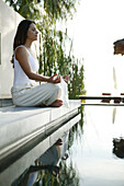 Woman meditating at the edge of a pool, Wellness, Relaxation, Health