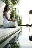 Frau beim Meditieren am Pool, Wellness, Entspannung, Sommer