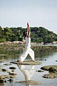 Frau macht Yoga am Strand, Wellness, Entspannung, Gesundheit, Thailand