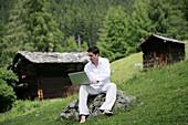 Mid adult man using a laptop, Heiligenblut, Hohe Tauern National Park, Carinthia, Austria