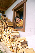 Woman looking out of a window and waving, Heiligenblut, Hohe Tauern National Park, Carinthia, Austria