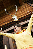 Woman stretching in front of alp lodge, Heiligenblut, Hohe Tauern National Park, Carinthia, Austria