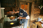 Man cooking scrambled eggs in alp lodge, Heiligenblut, Hohe Tauern National Park, Carinthia, Austria