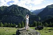 Woman practising yoga on a rock, Heiligenblut, Hohe Tauern National Park, Carinthia, Austria