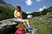 Woman sitting on a rock, chapel in background, Heiligenblut, Hohe Tauern National Park, Carinthia, Austria