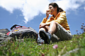 Woman sitting on grass while eating an apple, Heiligenblut, Hohe Tauern National Park, Carinthia, Austria