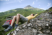 Woman lying on grass, mountains in background, Heiligenblut, Hohe Tauern National Park, Carinthia, Austria